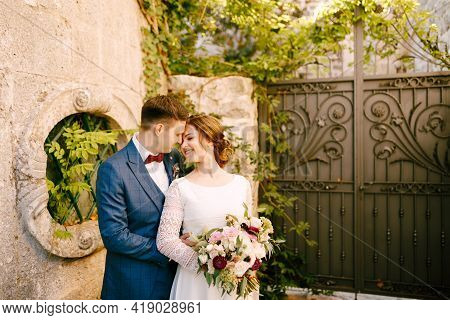 Smiling Bride And Groom Hugging On The Background Of Wrought Iron Gates In The Garden