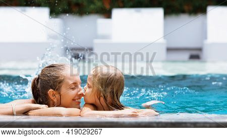 Happy People Have Fun At Pool Side Edge. Funny Photo Of Young Mother With Child Relaxing In Outdoor