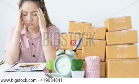 Young woman sitting on a desk is sad or depressed about a sales business, Anxiety and disappointment