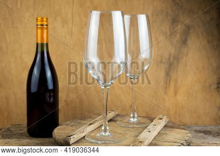 Two Empty Wine Glasses And A Bottle Of Wine Are On The Table. Romantic Dinner. Drinking Wine. Winegl