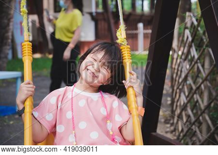 Happy Asian Girl Smile Sweet While Playing On Swing. Background Is Blurred Person Wear Mask Can Prev