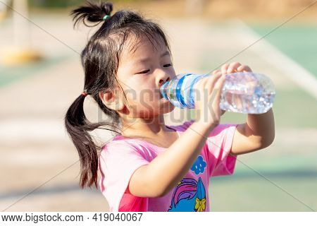 A 3-4 Years Old Girl Was Drinking Water To Quench Her Thirst Due To The Hot Weather. Kid Sweat On Th