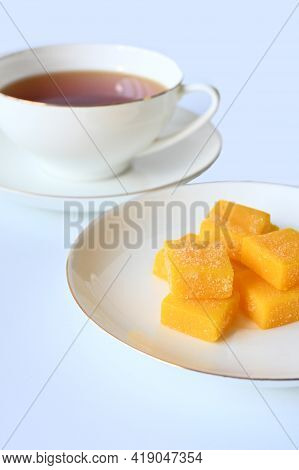 A Saucer With Delicious And Juicy Marmalade Orange Candies, In The Background With A Cup Of Black Te