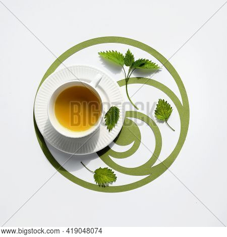 Nettle Tea Cup, Stinging Nettle Herb Leaves. Ornate Flat Lay, Green Paper Fibonacci Sequence Circles