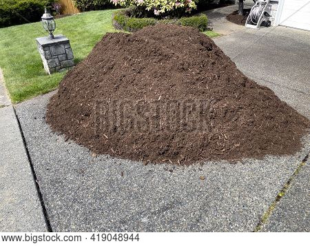 Pile Of Fresh Topsoil Dirt In Home Driveway For Lawn Maintenance
