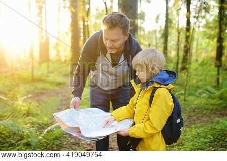 Schoolchild And His Mature Father Hiking Together And Exploring Nature. Little Boy With Dad Looking