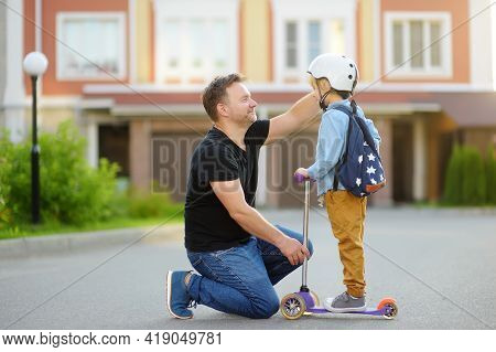 Little Boy With Scooter Says Goodbye And Hugging To His Father Before Going To School. Education For