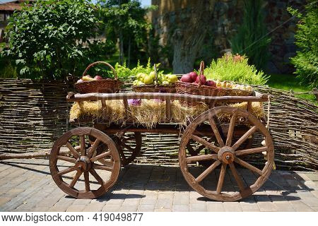Vintage Wooden Cart With Fruits And Vegetables For Sale In Market. Ripe Organic Apples And Corn In L