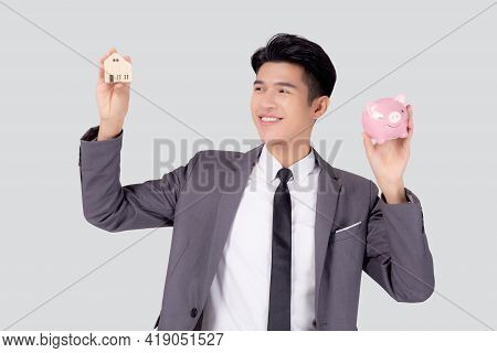 Young Asian Business Man Holding Home And Piggy Bank For Planning Saving Future, Insurance Agent And