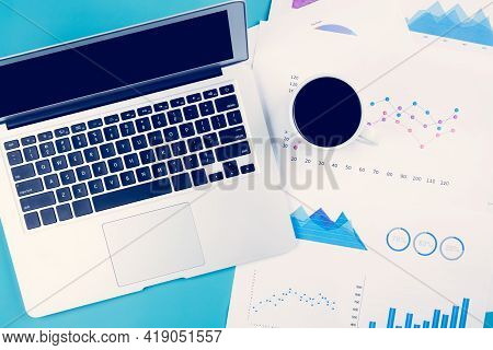 Laptop Computer And Documents Report Statistic Financial With Graph And Chart And Coffee On Desk, Fi