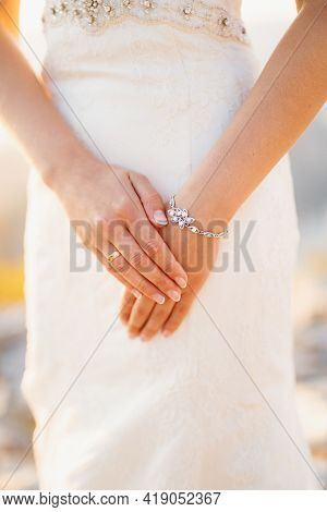 The Bride Folded Her Hands With A Wedding Ring On Her Finger And A Bracelet, Close-up