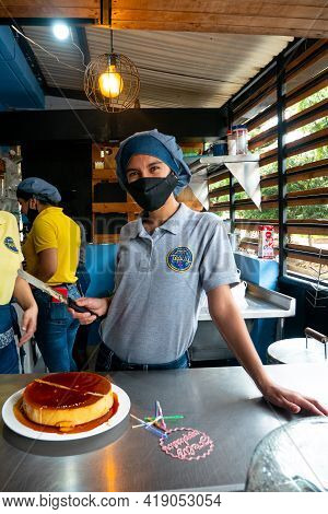 Medellin, Colombia - March 28 2021: Young Latin Woman In Gray Uniform And Cloth Hat Is Cutting A Fla