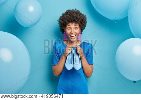 Positive Lovely Curly Haired Woman Dresses Up For Special Occasion Chooses High Heeled Shoes To Wear