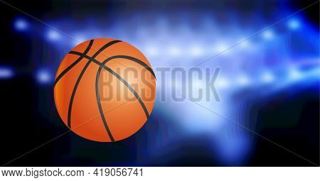 Composition of basketball in air over glowing blue spotlight of basketball arena. sports and competition concept digitally generated image.