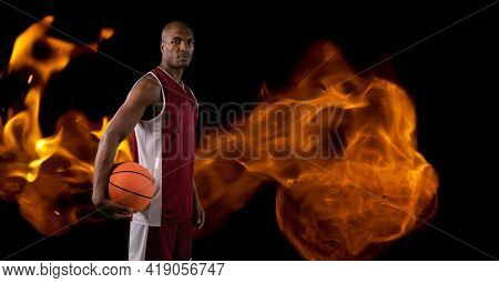 Composition of basketball player holding basketball over flames. sport and competition concept digitally generated image.