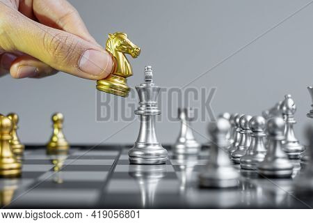 Businessman Hand Moving Gold Chess Knight Figure And Checkmate Opponent During Chessboard Competitio