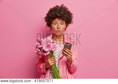 Photo Of Surprised Female Model Holds Bouquet Of Flowers Modern Smartphone Receives Unexpected Congr