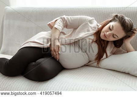 Stylish Pregnant Woman In The Last Month Resting On The Sofa At Home.