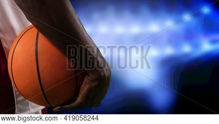 Composition of midsection of basketball player holding basketball over blue spotlights. sport and competition concept digitally generated image.