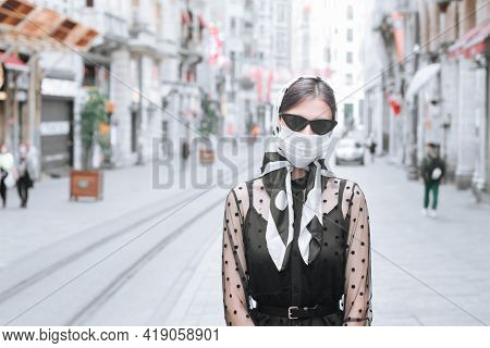 An Attractive Young Woman Wearing A Medical Mask Stands On Istiklal Street In Turkey During The Pand