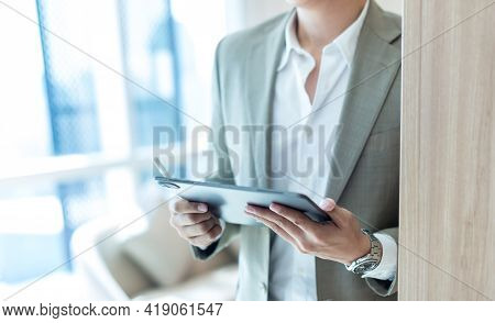 Businessman In Brown Suit Hand Holding Tablet For Writing And Thinking In Job At Workspace In Office