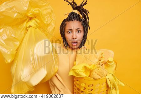 Surprised African American Woman With Combed Dreadlocks Carries Bag Full Of Litter Laundry Basket We