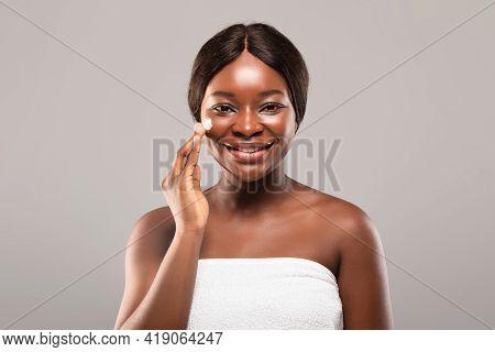 Skin Care Concept. Portrait Of Attractive African American Female Applying Moisturising Cream