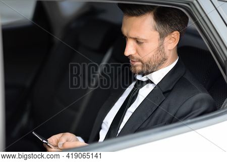 Wealthy Manager Sitting In Car And Using Smartphone