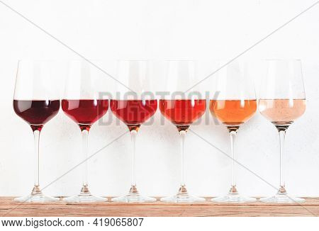 Rose Wine Glasses Set On Wine Tasting. Different Varieties, Colors And Shades Of Pink Wines On White