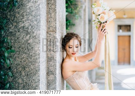 Bride Lowered Her Eyes, Leaning Against A Pillar With Raised Hands With A Bouquet Of Flowers. Lake C