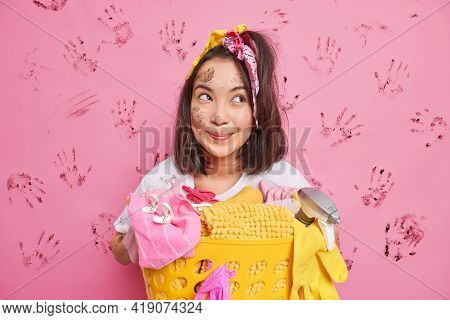 Cheerful Dreamy Brunette Housewife With Dark Hair Poses Near Basket Full Of Dirty Laundry Has Dirty