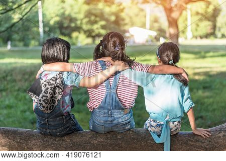 Children Friendship Concept With Happy Girl Kids In The Park Having Fun Sitting Under Tree Shade Pla