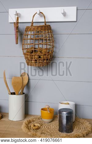 Modern Kitchen Interior With Grey Scandinavian-style Wood Paneling On The Wall, Walnuts In The Baske