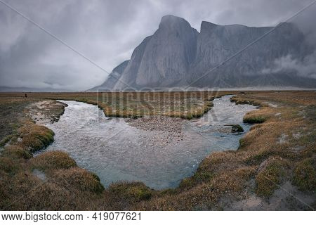 Majestic Rocks Tower Over Arctic Valley And River On Its Floor In Extra Cloudy, Harsh Weather. Tough