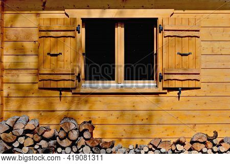 Wooden Facade With A Window And Open Shutters Of An Alpine Chalet  And Logs  Down