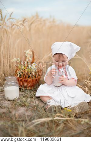 A Small Child Drinks Cow's Milk From A Glass In A Field Of Wheat. World Milk Day. Fresh, Healthy Mil