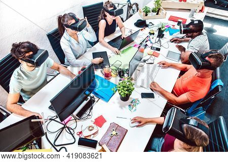 Group Of Employee Workers Concentrated On Virtual Reality Goggles At Startup Studio - Human Resource