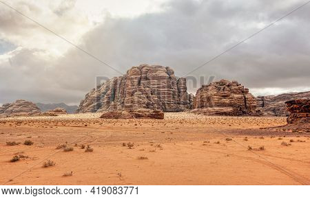 Rocky Massifs On Red Orange Sand Desert, Overcast Sky In Background - Typical Scenery In Wadi Rum, J