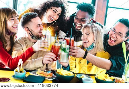 Happy Multiracial Friends Toasting Drinks With Open Face Masks - New Normal Life Style Concept With