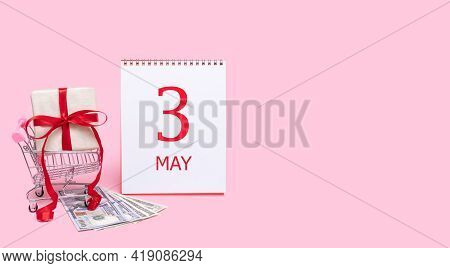 3rd Day Of May. A Gift Box In A Shopping Trolley, Dollars And A Calendar With The Date Of 3 May On A