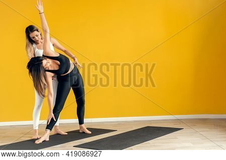 Yoga Class Instructor Helps Beginner To Make Asana Exercises. Happy Yoga Class With A Trainer. Exerc