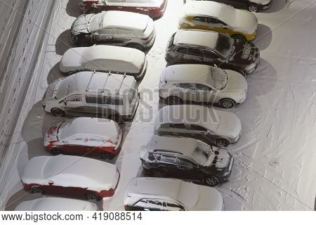 Many Parking Cars In Snow On Night Winter Parking Lots. Aerial View On Parking