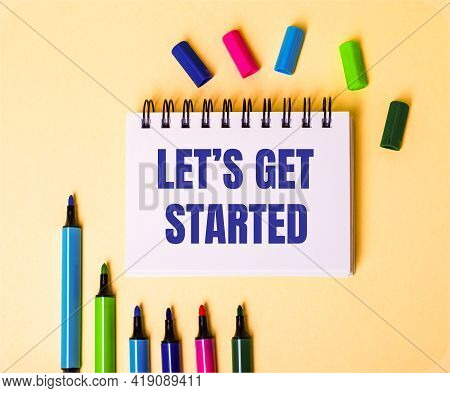 The Words Let Is Get Started Written In A White Notebook On A Beige Background Near Multi-colored Ma