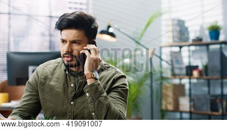 Close Up Portrait Of Hindu Serious Young Handsome Male Worker Speaking On Smartphone Having Call Wit