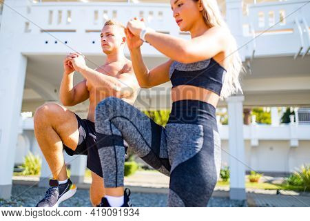 Young Couple In Sport Clothing Doing Stretching Exercises Together Outdoor In Summer Beach Tropics