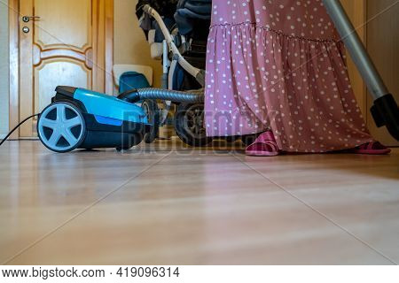 Housewife Vacuum Cleaner Vacuuming The Floor In The Apartment