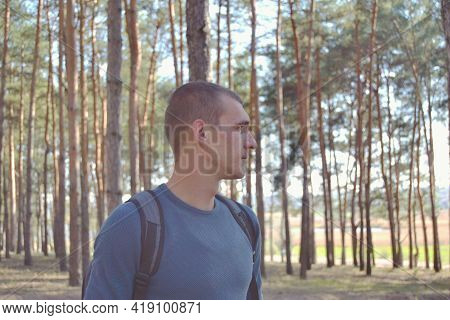 Young Man Portrait. Male Hiker Walking In Forest.