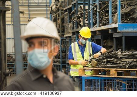 Men Work Together, Wear Safety Facemask And Repair Auto Part. Asian Man Repair Auto Part Behind Cauc