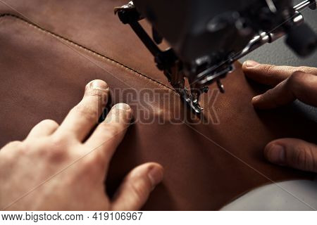 Working Process Of Leather Craftsman. Tanner Or Skinner Sews Leather On A Special Sewing Machine, Cl