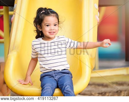 A Cute Asian Girl Resting After Having Fun Playing The Slider In The Playground